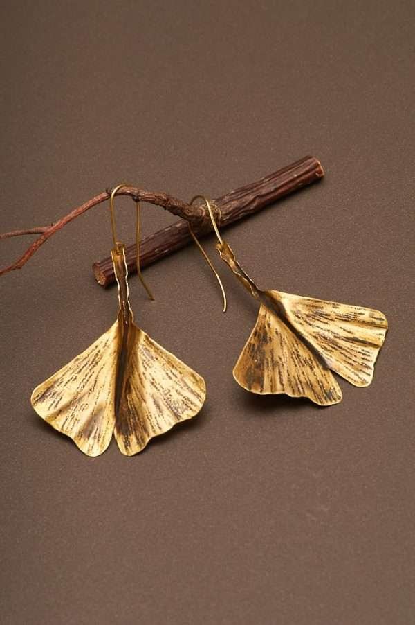 Ginkgo Fly Gold Earrings displayed on the nice background with branch and designed by Ertiusn