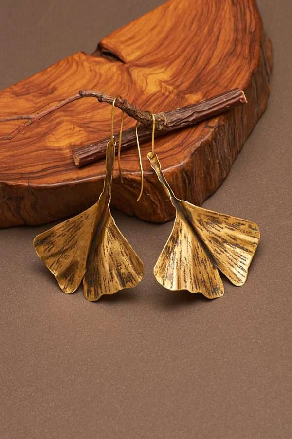 Ginkgo Fly Gold Earrings displayed on the nice background with branch and wood designed by Ertiusn