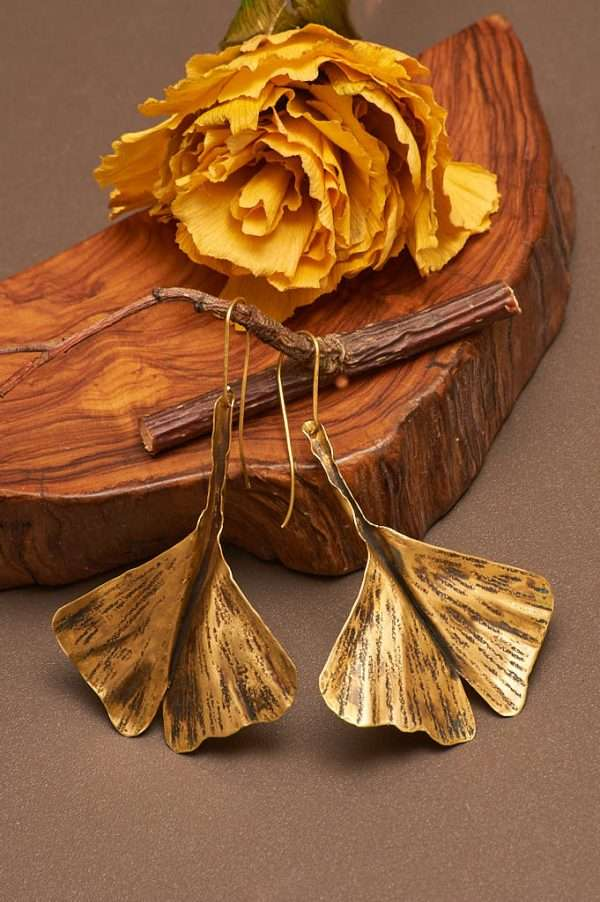 Ginkgo Fly Gold Earrings displayed on the nice background with branch and wood and natural flower designed by Ertiusn