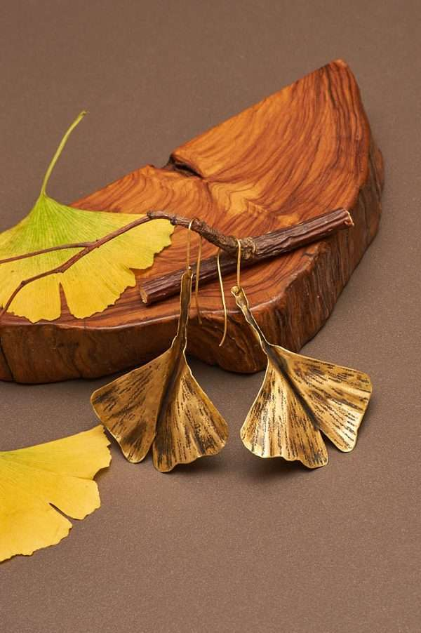 Ginkgo Fly Gold Earrings displayed on the nice background with branch and wood and ginkgo leaves designed by Ertiusn